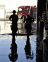 Two Hillsboro firefighters push water from an unheated warehouse flooded by a broken sprinkler pipe.