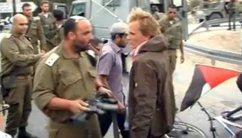 Israeli Lieutenant-Colonel Eisner prepares to attack a a peace activist with his rifle