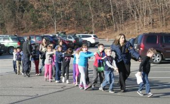 Children are led from Sandy Hook Elementary School in Newtown, Conn., on Friday after a reported shooting there.   Shannon Hicks / The Newtown Bee.