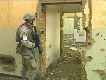 American soldier peers into an old Russian factory that is a ruin today, as much of war-torn Kabul is