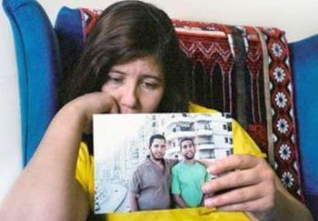 Ziyad Yaghi's mother, Laila Yaghi, holds his photograph.