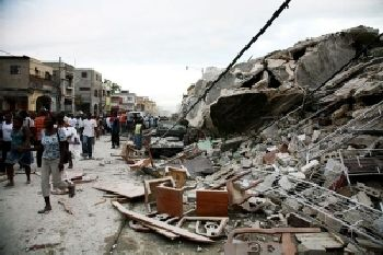 Haitians walk past damaged buildings on January 12 in Port-au-Prince
