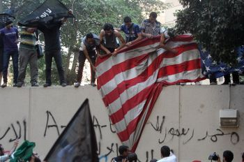 Egyptian protesters tear down the US flag during a demonstration at the US Embassy in September 2012 [EPA]