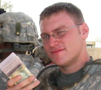 Lt. Brian Reynolds, an officer with the 101st Airborne in Iraq last summer, holds money that will be paid to Sunni militia members.  Salem-News.com photo by Tim King