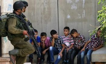 Two Israeli soldiers guard Palestinian children in Hebron