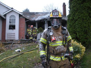 A firefighter covered in foam exits the house after dousing hot spots
