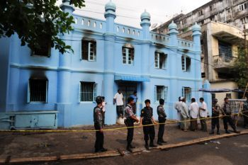Authorities stand outside a madrasa in east Rangoon where 13 Muslim schoolchildren died after a fire in April. (Photo: The Irrawaddy / Steve Tickner)